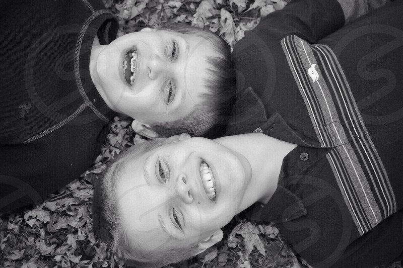two boys lying in leaves smiling grayscale photo photo
