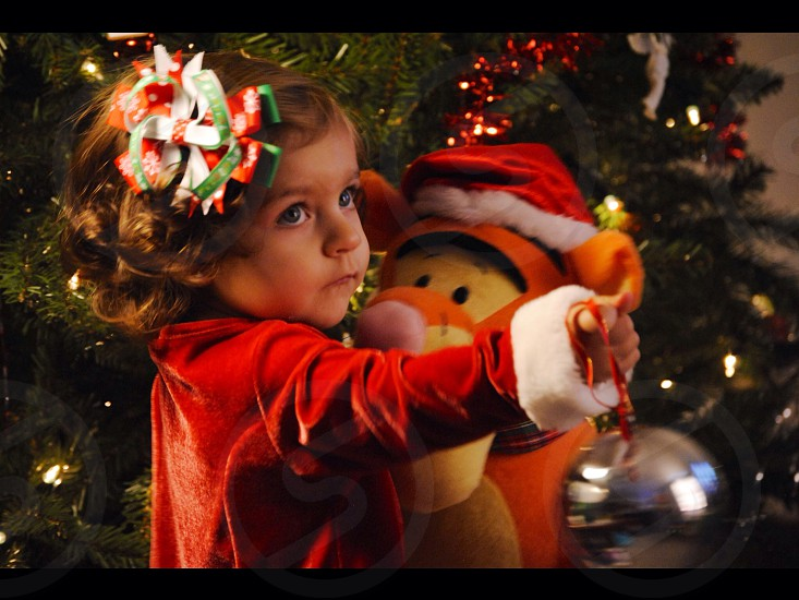 toddler in red Santa Claus costume holds tigger plush toy photo
