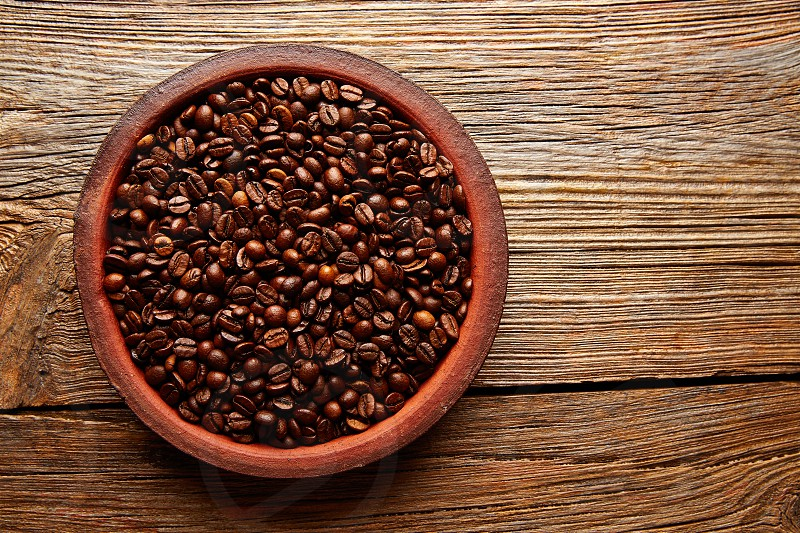 Coffee beans in a clay dish with nice texture on aged wood table background photo