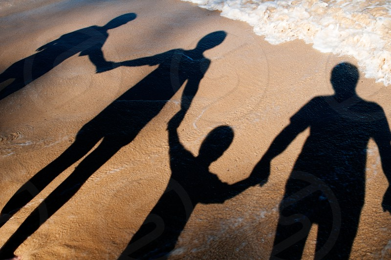 family togetherness people holding hands shadow sandy beach summer holiday vacation concepts children adults horizontal photo