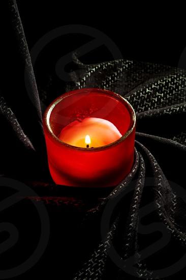 candle on a red glass holder over a black fabric background photo