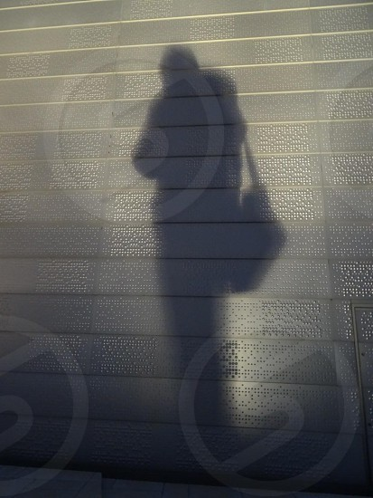 man with back shadow on the grey wall photo