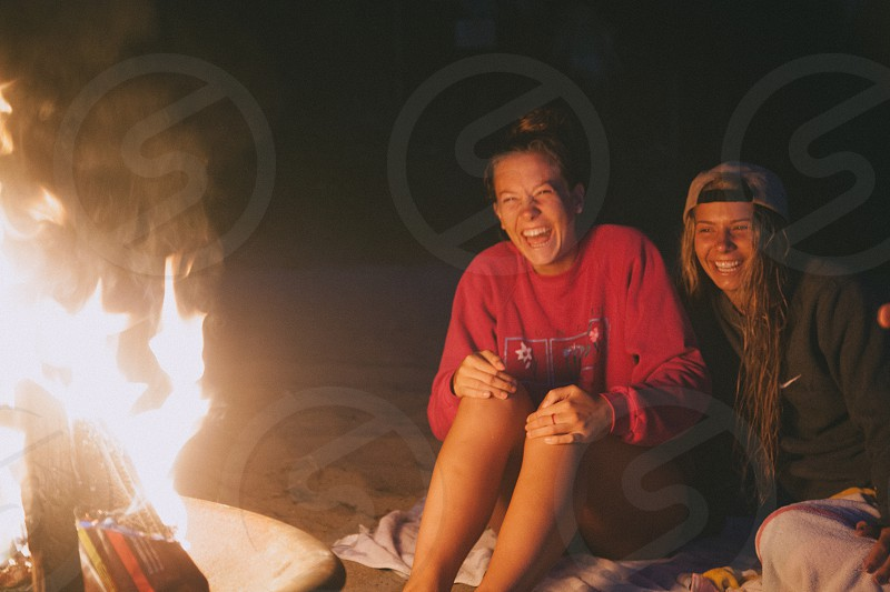 2 women smiling while sitting on the ground near fire pit during nighttime photo