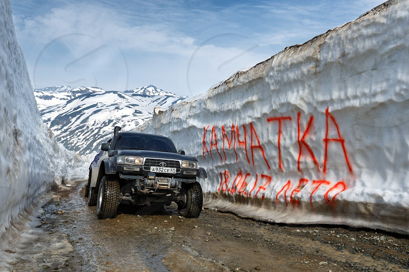 KAMCHATKA PENINSULA RUSSIAN FAR EAST - JUNE 18 2017: Japanese extreme off-road expedition car Toyota Land Cruiser driving on mountain road in snow tunnel surrounded by high snowdrifts. photo