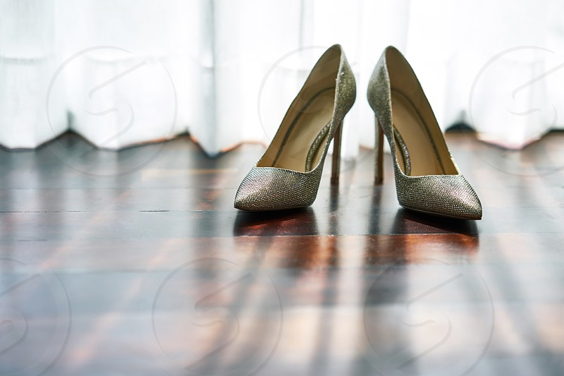 Women high heels shoes with glittering and shiny texture on the wooden floor with light and shadow photo