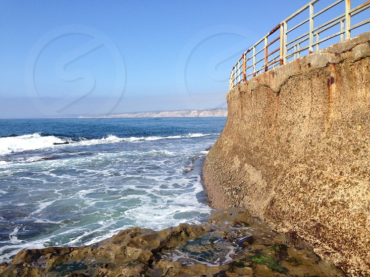 ocean waves and brown concrete structure with handrails photo