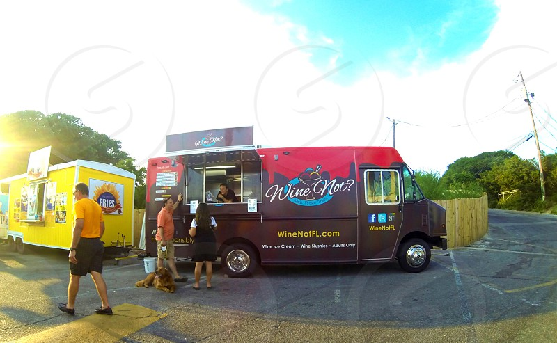 man and woman standing in front on red-and-maroon Wine Not? food truck during daytime photo