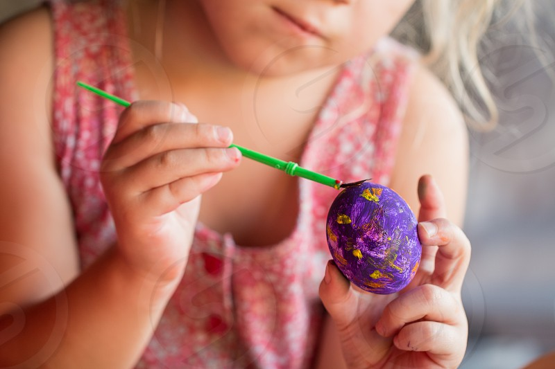 kid painting easter eggs with brush photo