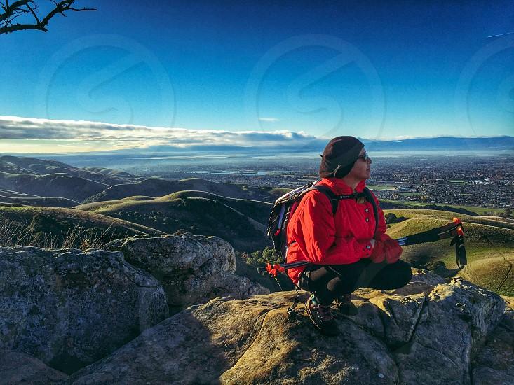Woman hiking reflecting jacket kneeling view exercising  photo