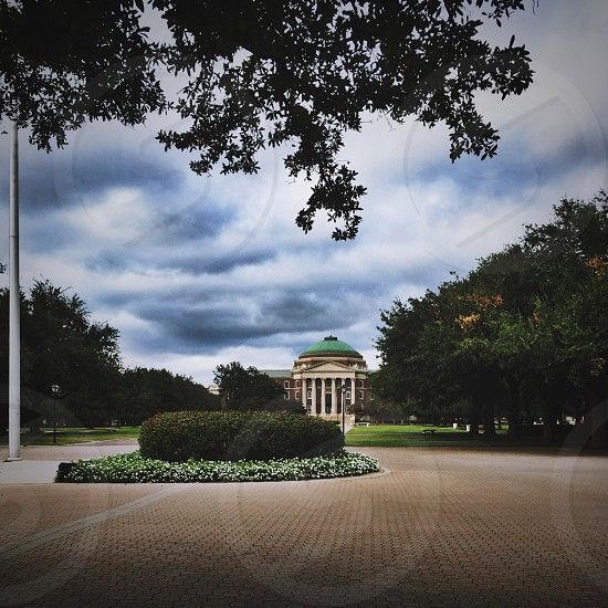 round driveway in front of a building with white columns photo