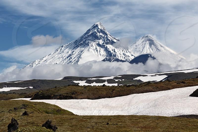Beautiful mountain landscape of Kamchatka Peninsula: view on Kamen Volcano active Klyuchevskoy Volcano and active Bezymianny Volcano on a sunny day. Russia Far East Kamchatka. photo
