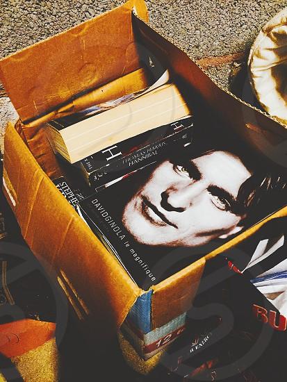 davidginola le magnifique book besides another books insides brown cardboard box photo