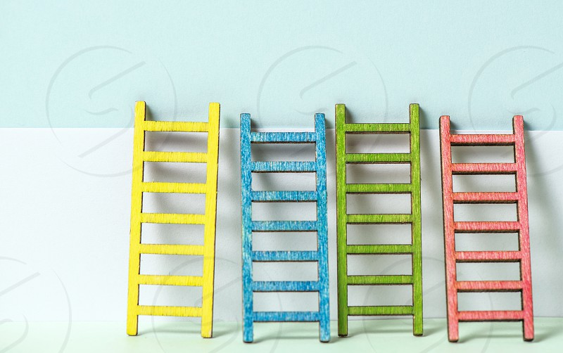 Multicoloured ladders on wall. Pastel tones. Concept for success and growth. Business metaphors. photo