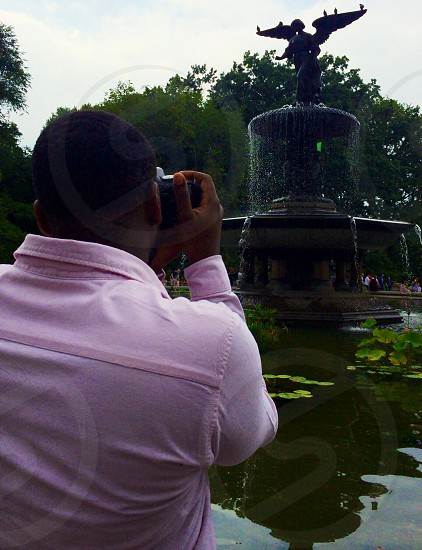 man in pink dress shirt taking pictures of black angel statues garden fountain photo