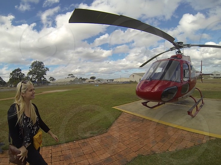 woman standing in front of red helicopter photo