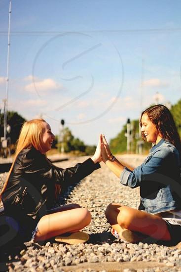 2 woman sitting on train tracks photo