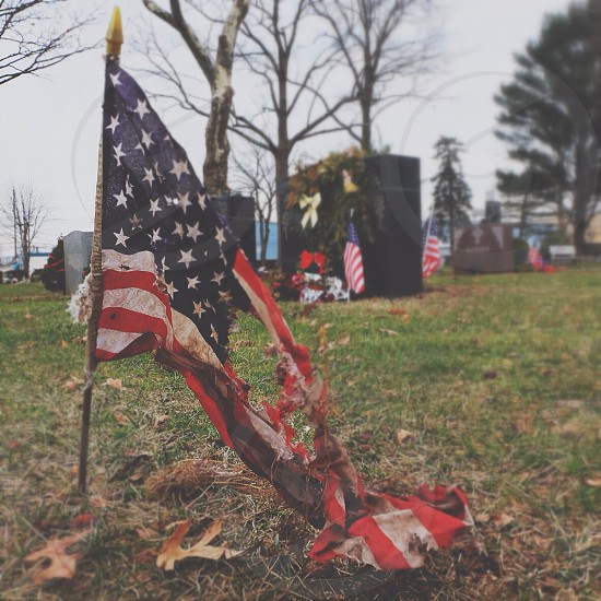 torn american flag on top of brown and green grass photo