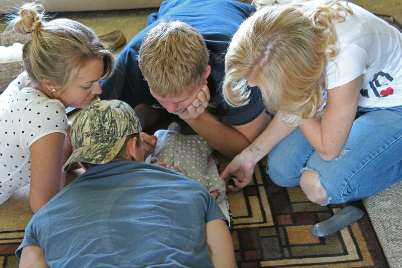 two women and two men looking at baby wearing gray shirt sitting and lying on brown and multicolored mat photo