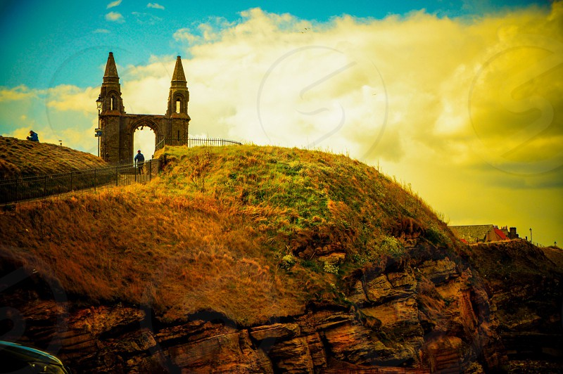 landscape photography of person walking near castle on hill during golden hour photo