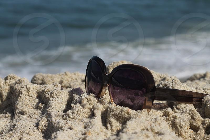 black sunglasses on brown beach sand photo