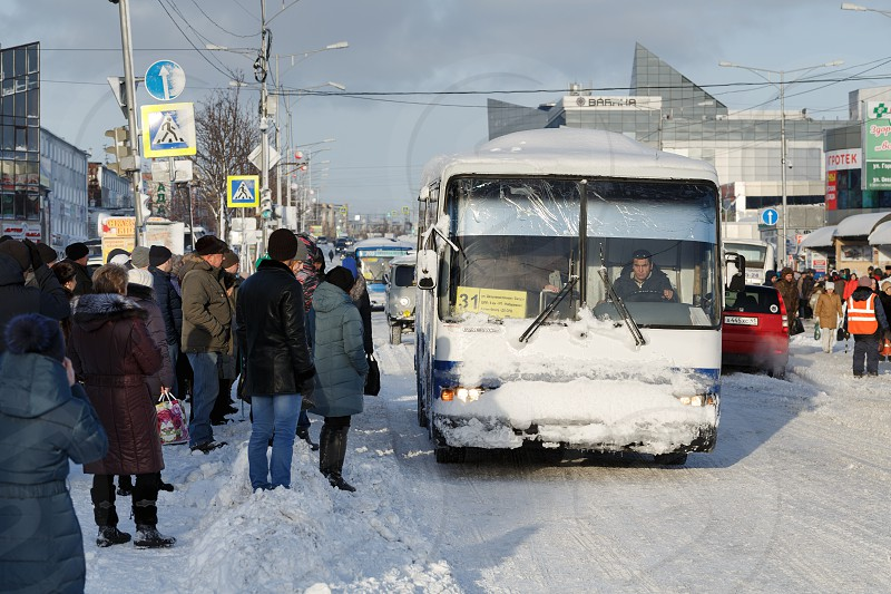 PETROPAVLOVSK CITY KAMCHATKA RUSSIA - DEC 27 2017: Winter city landscape after snowy cyclone - people in anticipation of public transport are standing on carriageway of city road in bus stop area photo