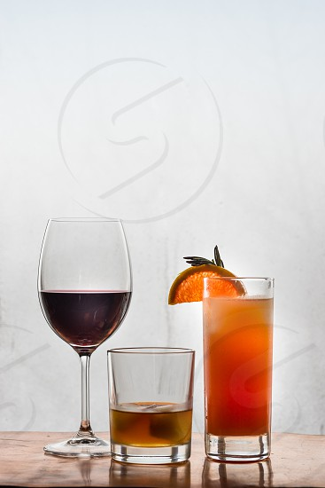 A glass of red wine whiskey with ice in a glass and a cocktail with a slice of grapefruit and a sprig of rosemary. photo