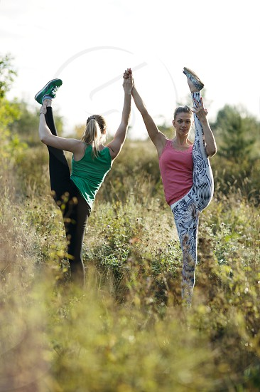 Two supple athletic women working out together as they practise a routine outdoors in long grass photo