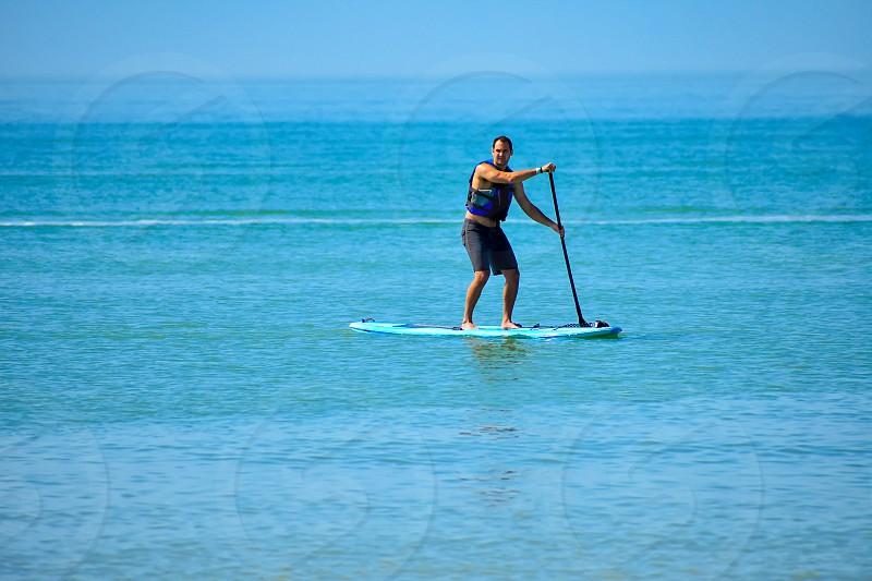St. Pete Beach Florida. January 25 2019.  Man enjoying stand up paddle board on blue sea background (1) photo