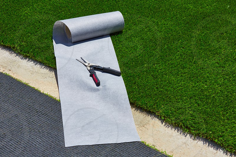 Artificial grass turf installation in garden with tools and joint roll photo
