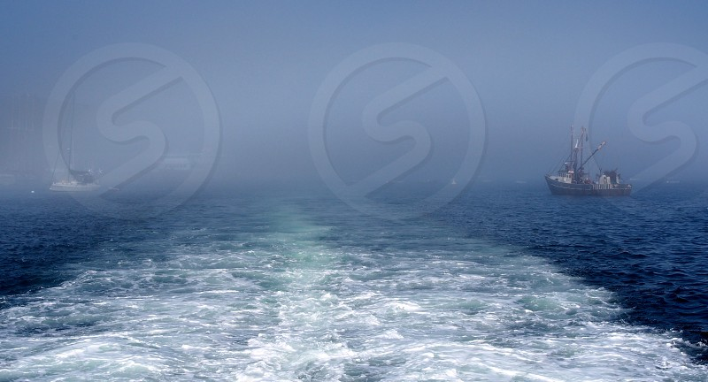 Fishing boats. Wake. Ocean. photo