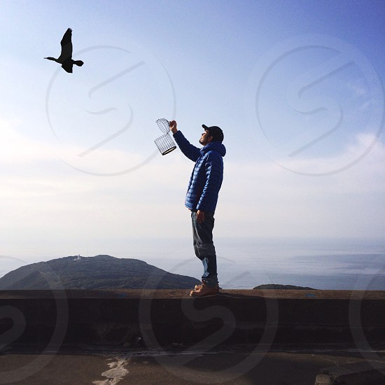 man in blue hoodie and black cap holding container photo