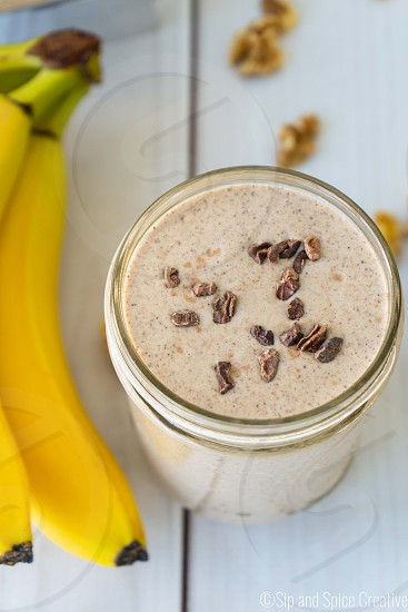 One glass mason jar filled with a banana chocolate walnut smoothie on a white wood background. photo