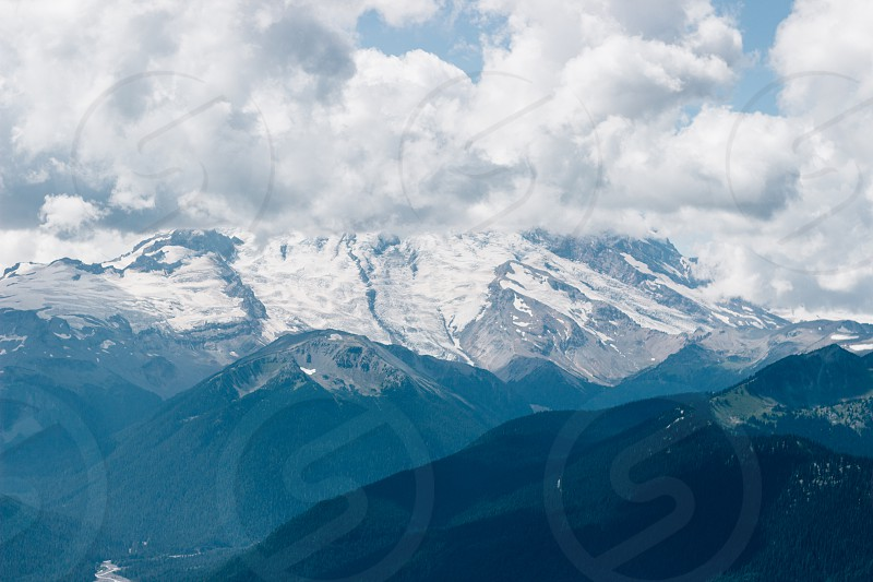 cumulus cloud over snowy mountain photo