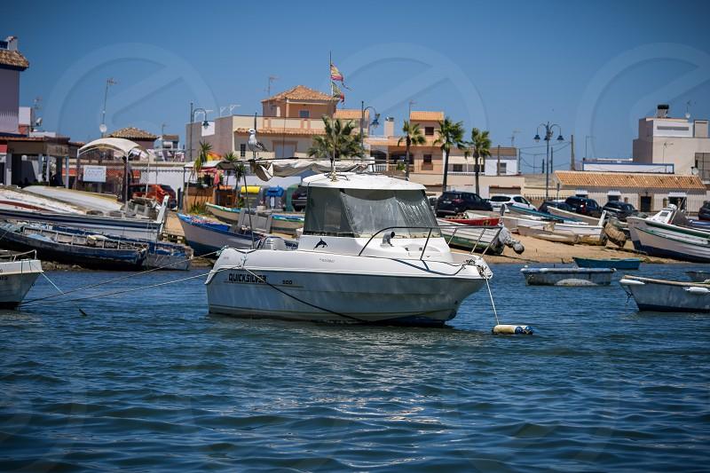 A solitary boat floating in the middle of a marina in a small town in the south of Spain photo