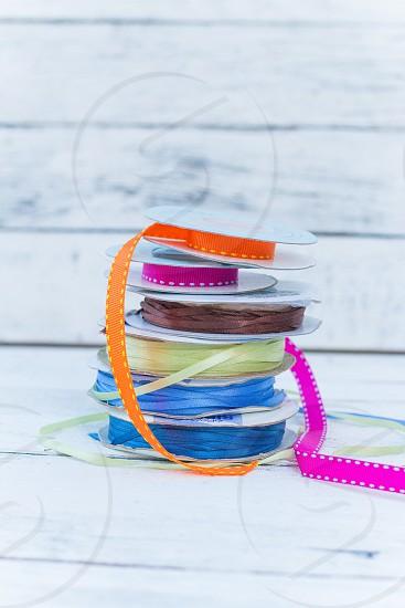 Stack of colourful ribbon on plain white wood background photo