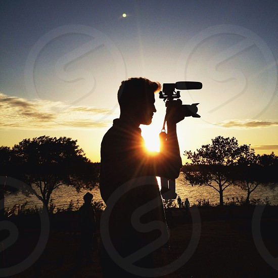 person taking picture with sunrise background photo