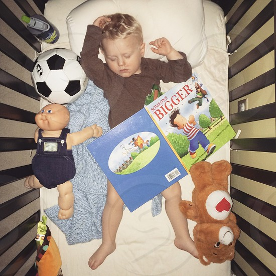 toddler wearing brown long sleeve shirt laying on white bed near white and black soccer ball photo