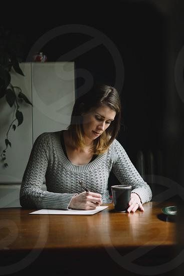 lifestyle writing letter correspondence moody lighting home female photo