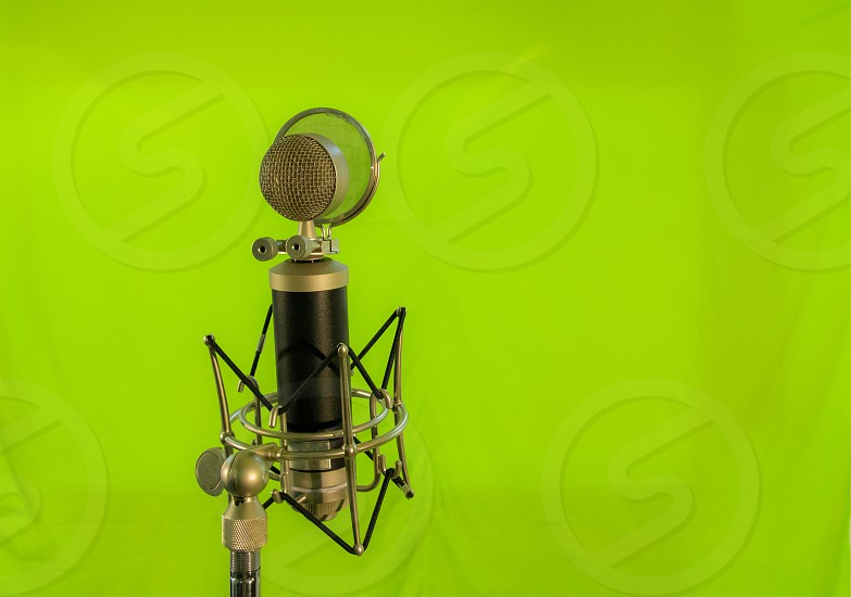 Vocal condenser microphone with wind screen isolated on green background. photo