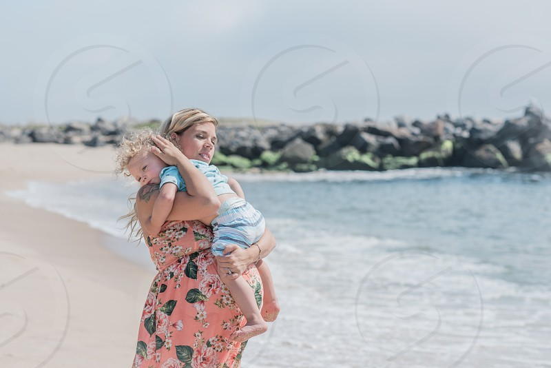 Photograph of a pregnant blonde white woman facing the ocean and holding her blonde white toddler son on the beach. photo