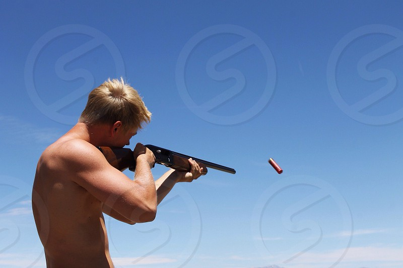 man firing a riffle photo