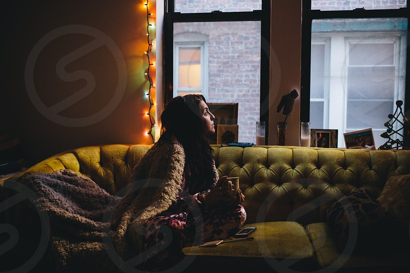 woman in brown jacket sitting on brown couch photo