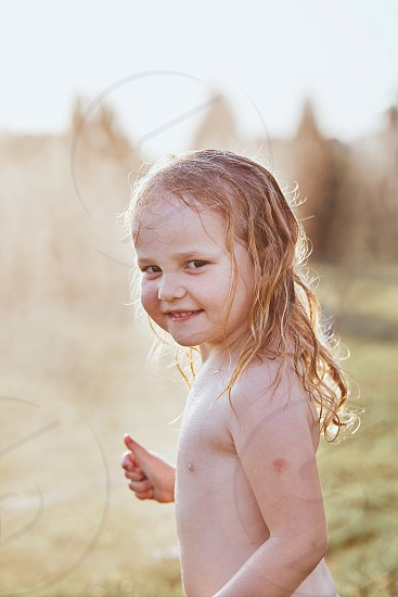 Little cute adorable girl enjoying a cool water sprayed by her mother during hot summer day in backyard. Candid people real moments authentic situations photo