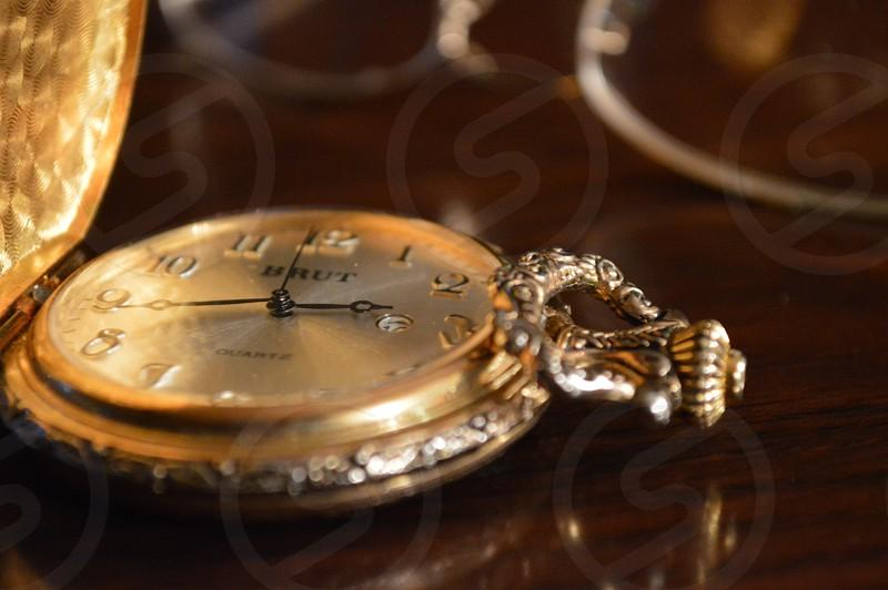 gold pocket watch reading 2:43 photo