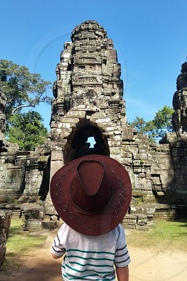 person wearing cowboy hat looking at stoned archway photo