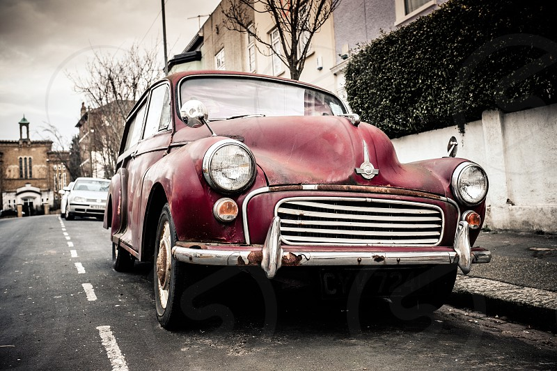Vintage car Maroon burgundy Morris minor parked in a domestic street in Woolwich England classic car muted colours  photo