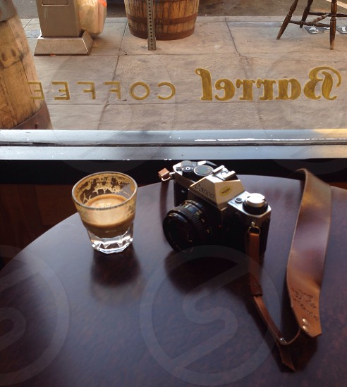 black and gray dslr camera beside clear shot glass on brown table photo