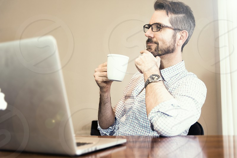 Professional day trader at desk enjoying coffee. photo