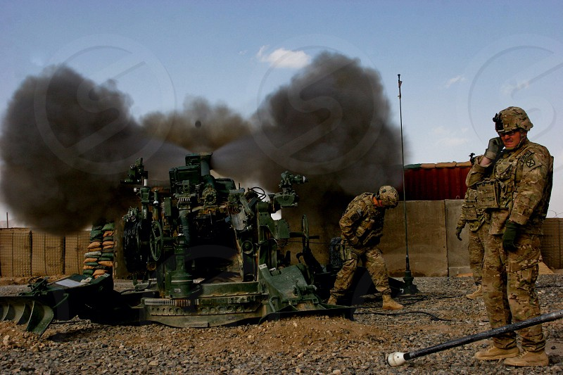 A soldier firing his last round of deployment into a neighboring Taliban stronghold  photo
