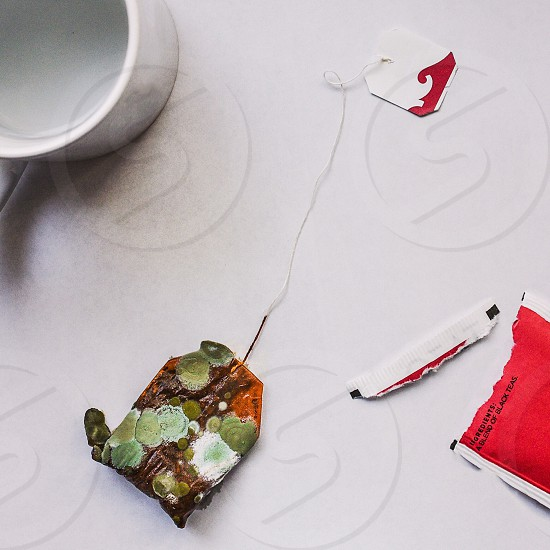 green brown and orange teabag white ceramic mug and red and white paper sachet on white tabletop photo